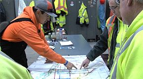 Streets Workers discussing a map of snow plow routes